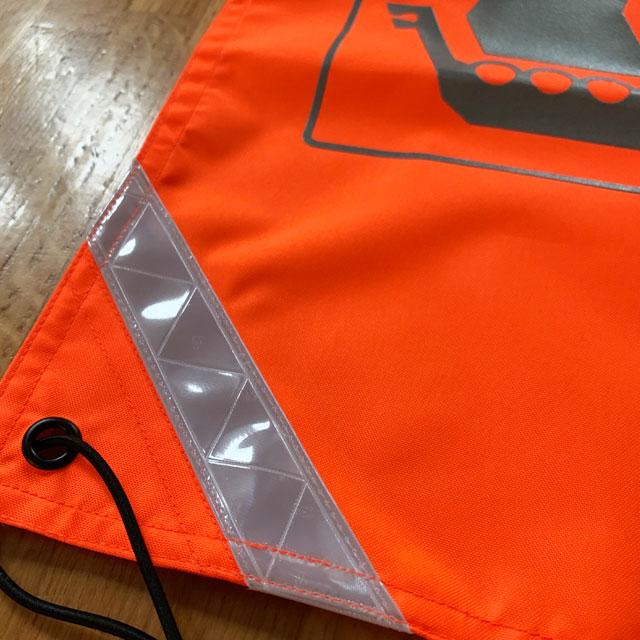 Orange Ruck Signal Panel Marker reflective stripe in corner photoed indoors.