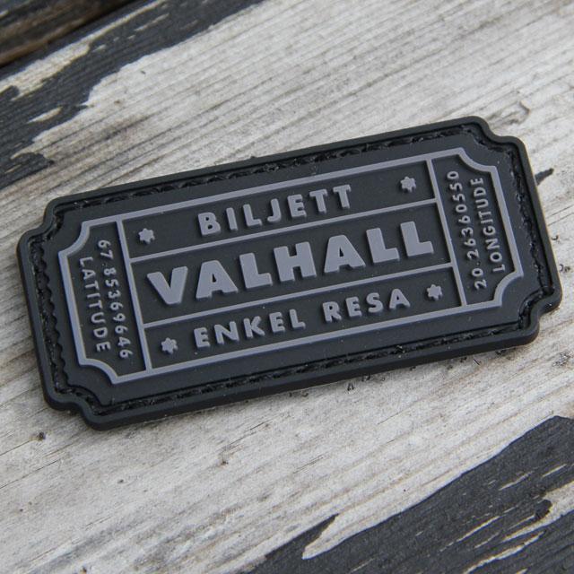 Ett Biljett Valhall PVC Svart/Grå märke mot träbakgrund.