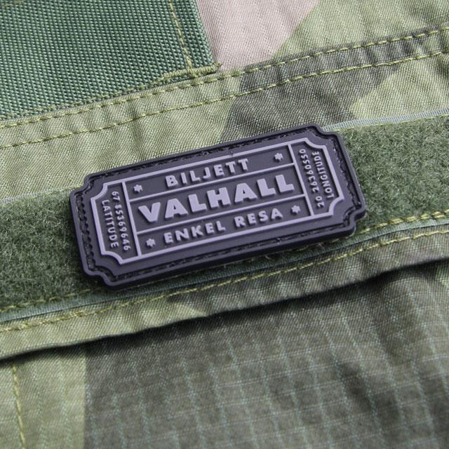 Här syns ett Biljett Valhall PVC Svart/Grå monterat på bröstfickan på en Field Shirt M90.