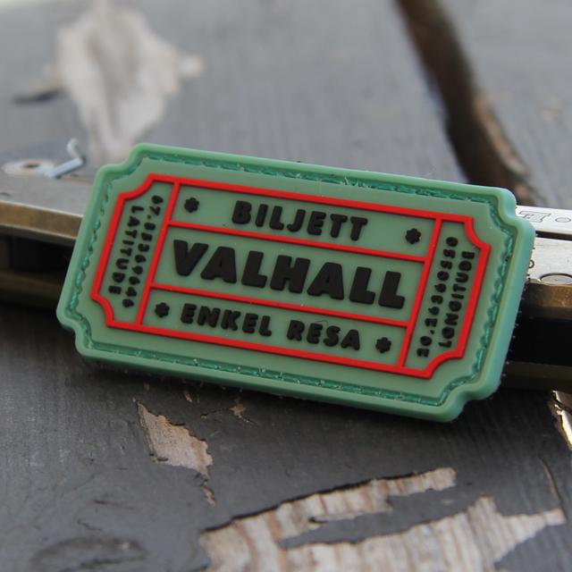 Ett Biljett Valhall PVC Ljusgrön märke mot en träbakgrund.