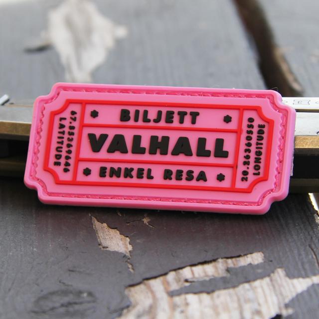 Ett Biljett Valhall PVC Rosa märke mot en bakgrund i trä.