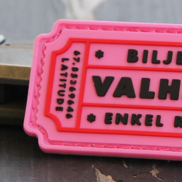 En närbild på ett Biljett Valhall PVC Rosa märke.
