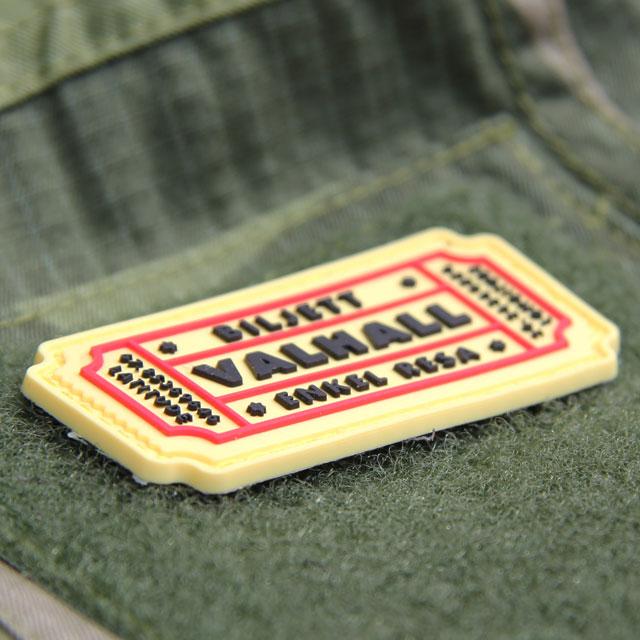 Ett Biljett Valhall PVC Gul/Röd monterat på ärmen på en Field Shirt M90.