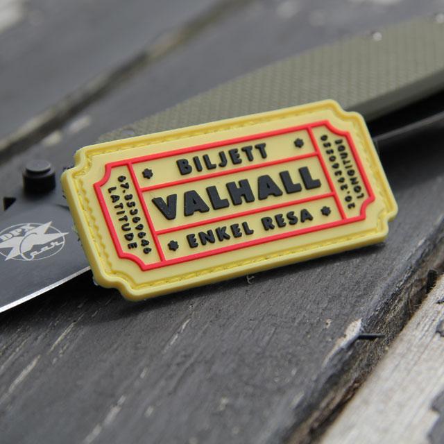 Ett Biljett Valhall PVC Gul/Röd märke med en kniv i bakgrunden för storleksjämförelse.