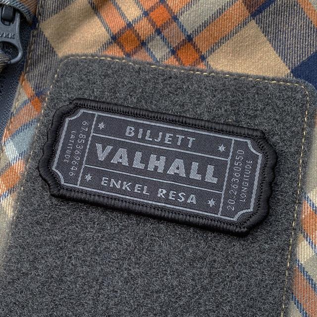 En Biljett Valhall Svart/Grå monterad med kardborre på en rutig skjorta