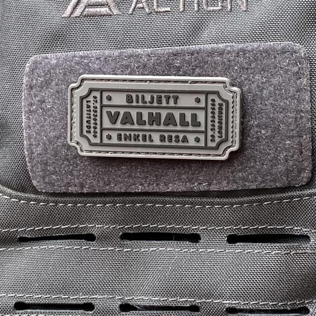Närbild på en monterad Biljett Valhall PVC Grå på en grå ryggsäck