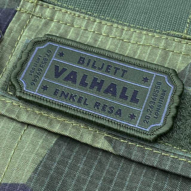 En Biljett Valhall Militärgrön monterad med kardborre på en M90 Shirt