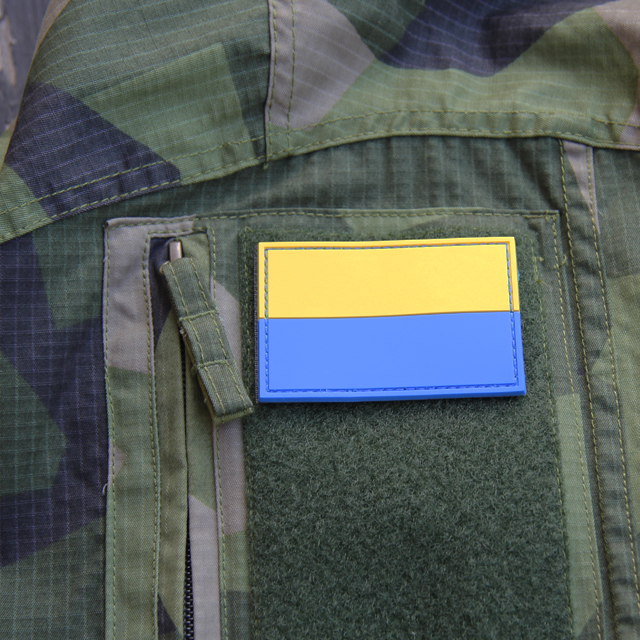 Blå-Gul Hook PVC Patch mounted on arm of a M90 camouflage jacket.