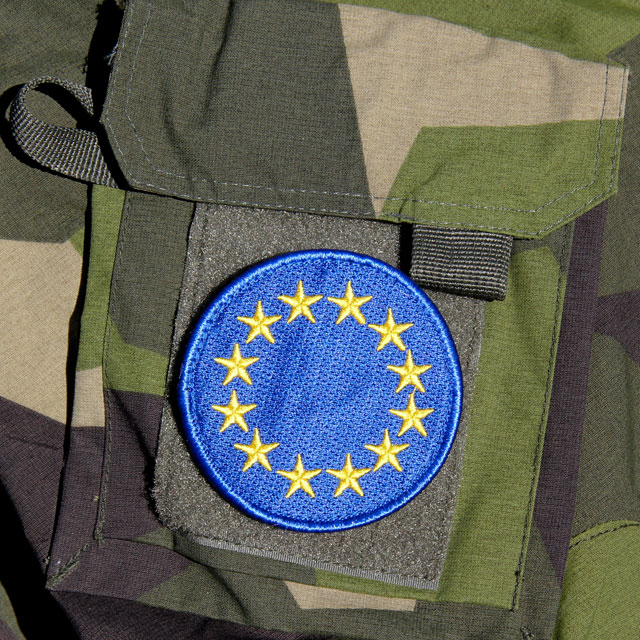 A mounted EU Blue Embroidered Patch on a M90 camouflage jacket sleeve.