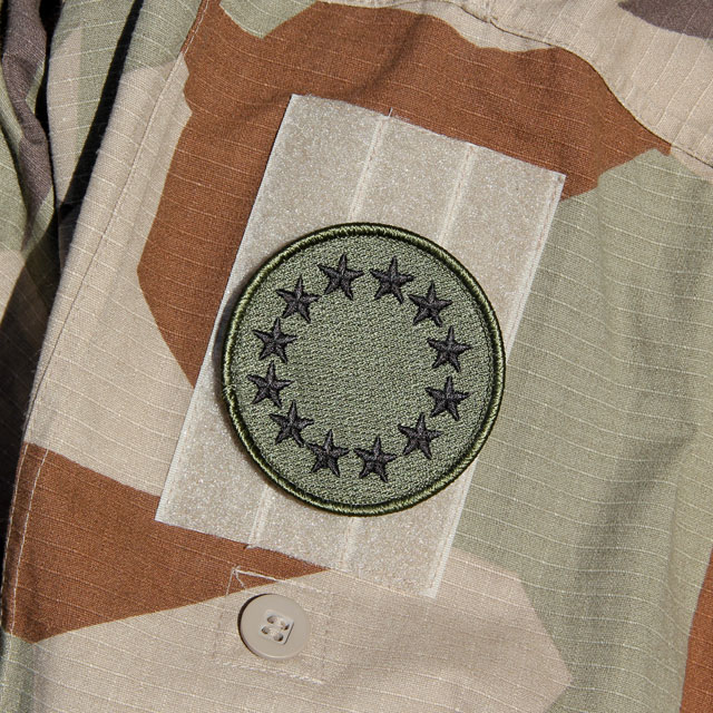 A EU Green Embroidered Patch mounted on a M90K Desert Jacket arm.
