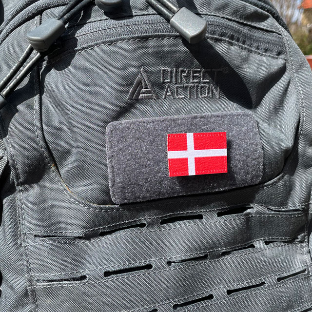 A Denmark Flag Hook Patch Small from TAC-UP GEAR mounted on a grey rucksack seen from an angle