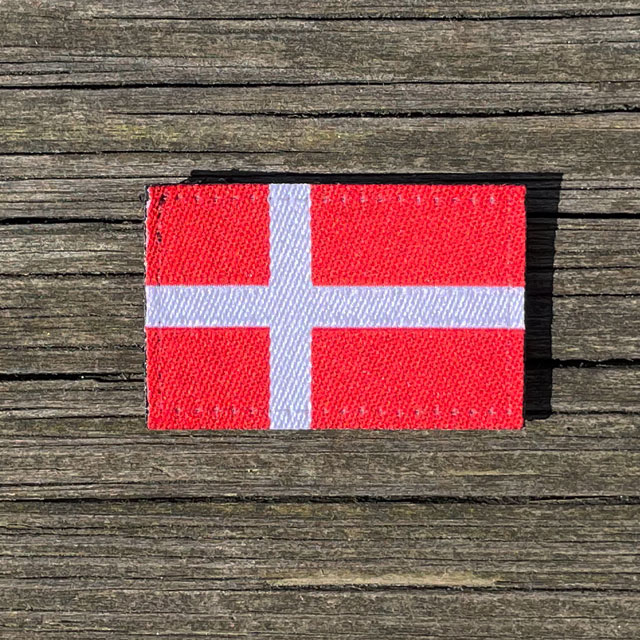 Denmark Flag Hook Patch Small from TAC-UP GEAR lying flat on wood