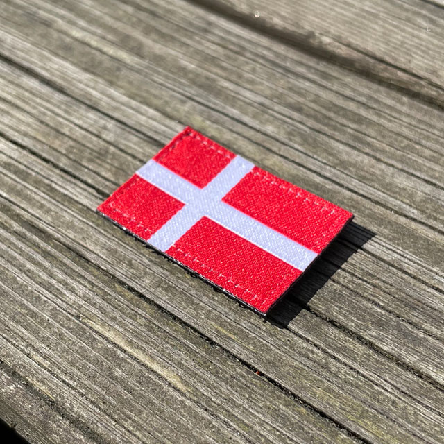 Denmark Flag Hook Patch Small from TAC-UP GEAR lying flat on wood seen from an angle