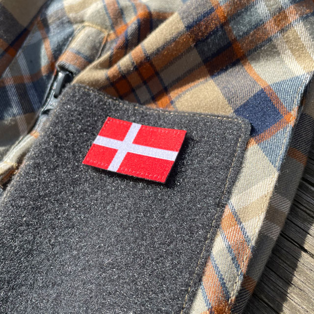 A Denmark Flag Hook Patch Small from TAC-UP GEAR mounted on loop fabric on a shirt