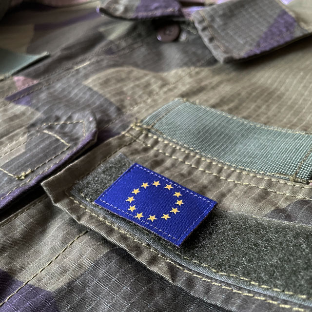A Blue and yellow EU Flag Hook Patch Small from TAC-UP GEAR on a M90 shirt breast