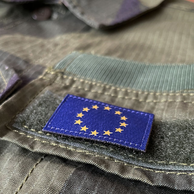 A Blue and yellow EU Flag Hook Patch Small from TAC-UP GEAR on a M90 Shirt seen from an angle