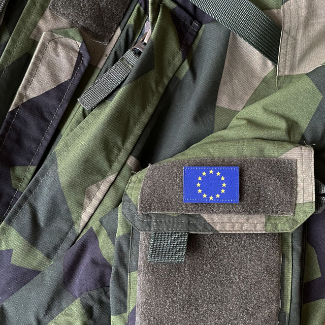A Blue and yellow EU Flag Hook Patch Small from TAC-UP GEAR on a M90 NCWR Jacket arm pocket seen full front