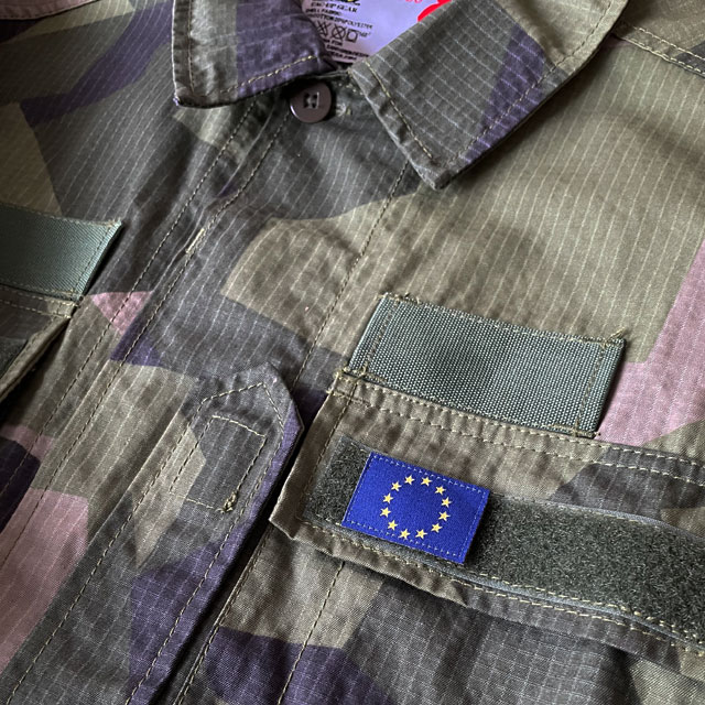 A Blue and yellow EU Flag Hook Patch Small from TAC-UP GEAR on a M90 shirt breast loop seen from a distance