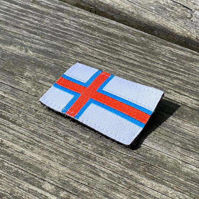 Faroese Flag Hook Patch Small seen from an angle lying on wooded floor