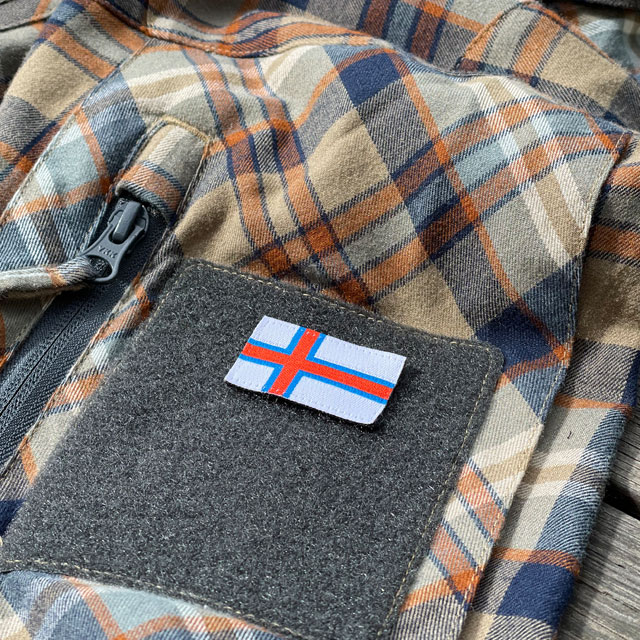 A Faroese Flag Hook Patch Small seen from an angle mounted on a shirt