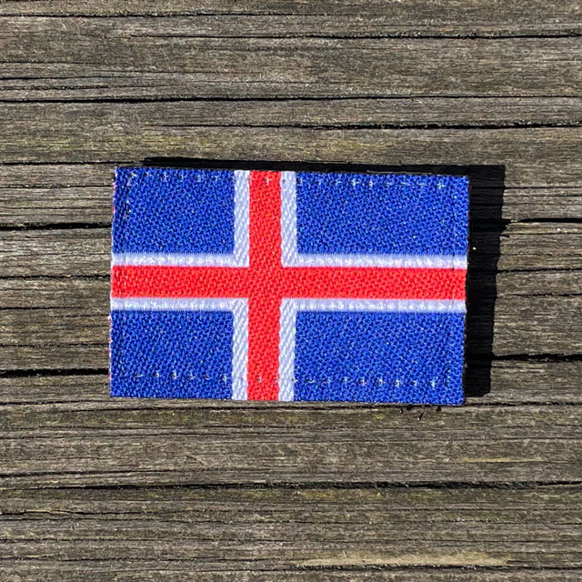 A Iceland Flag Hook Patch Small from TAC-UP GEAR laying on wooded a plank