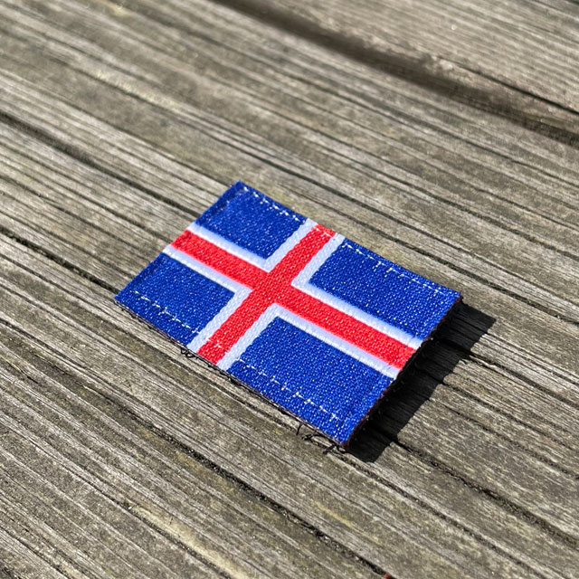 A Iceland Flag Hook Patch Small from TAC-UP GEAR laying on wooded a plank seen from an angle