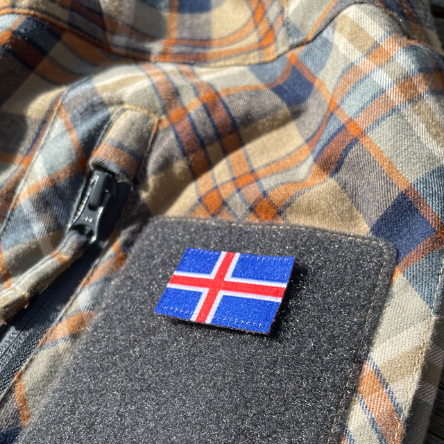 A Iceland Flag Hook Patch Small from TAC-UP GEAR mounted on velcro sleeve on a shirt seen at an angle