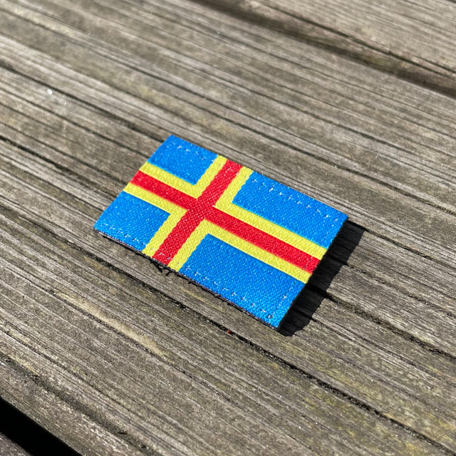 A Åland Flag Hook Patch Small from TAC-UP GEAR lying flat on a wooden plank seen from an angle