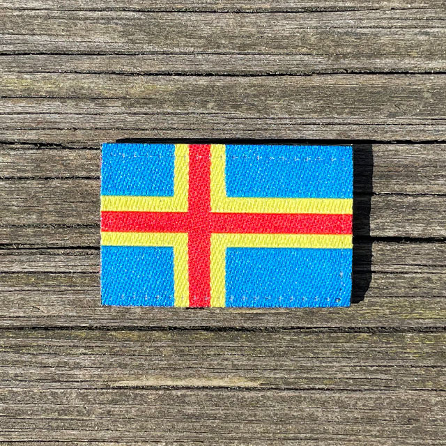 Åland Flag Hook Patch Small from TAC-UP GEAR lying flat on a wooden plank