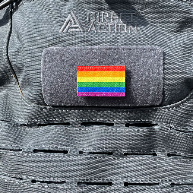 A Rainbow Flag Hook Patch Small lying mounted on a rucksack