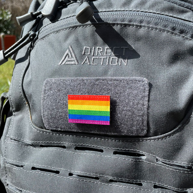 A Rainbow Flag Hook Patch Small lying mounted on a rucksack seen from an angle