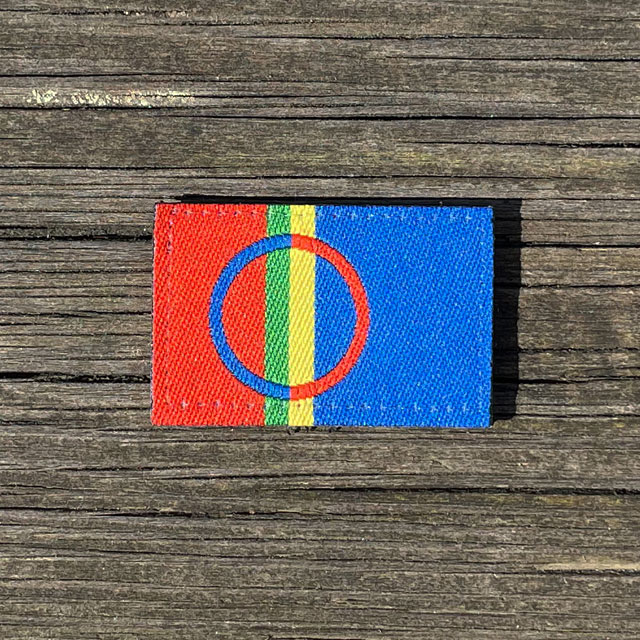 A Sámi Flag Hook Patch Small from TAC-UP GEAR laying flat on a wooded floor