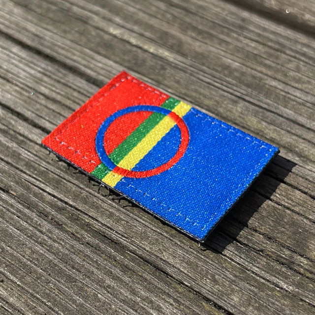 A Sámi Flag Hook Patch Small from TAC-UP GEAR laying flat on a wooded floor seen from an angle