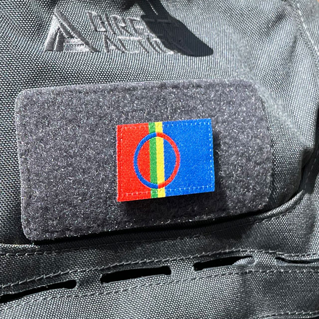 A Sámi Flag Hook Patch Small from TAC-UP GEAR mounted with hook and loop on a grey rucksack seen from an angle