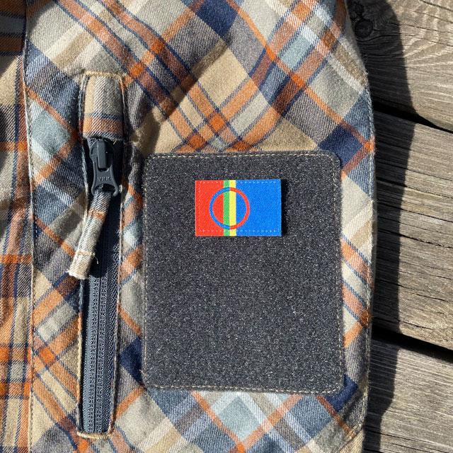 A Sámi Flag Hook Patch Small from TAC-UP GEAR mounted with hook and loop on a shirt sleeve