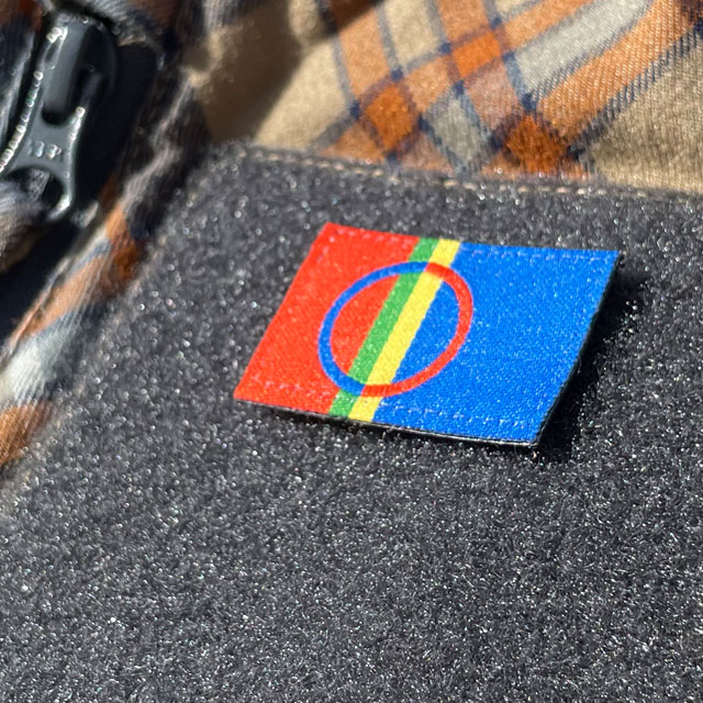 A close up picture of a Sámi Flag Hook Patch Small from TAC-UP GEAR mounted with hook and loop on a shirt sleeve
