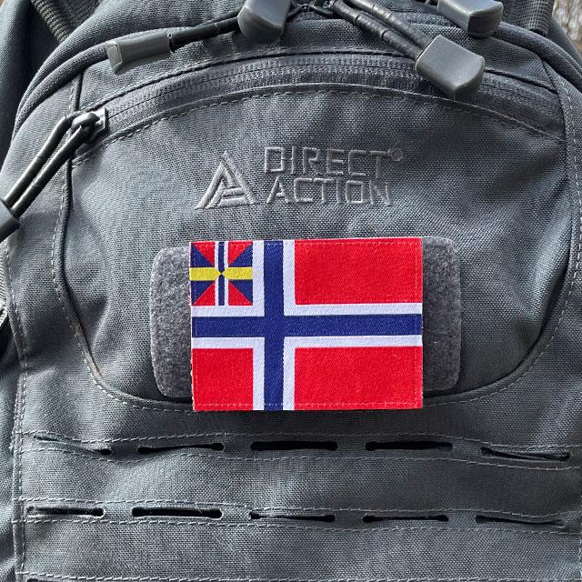 Norges handelsflagga 1844–1898/99 som ett tygmärke med kardborre på baksidan färst på en grå ryggsäck sedd framifrån