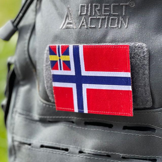 Norges handelsflagga 1844–1898/99 som ett tygmärke med kardborre på baksidan färst på en grå ryggsäck