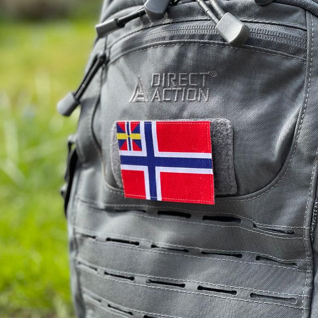 Ett tygmärke med kardborre: Norges handelsflagga 1844–1898/99 som ses från sidan på en grå ryggsäck