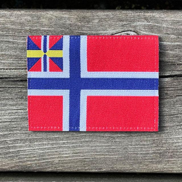 Norges handelsflagga 1844–1898/99 som ett tygmärke och som ligger på ett trägolv