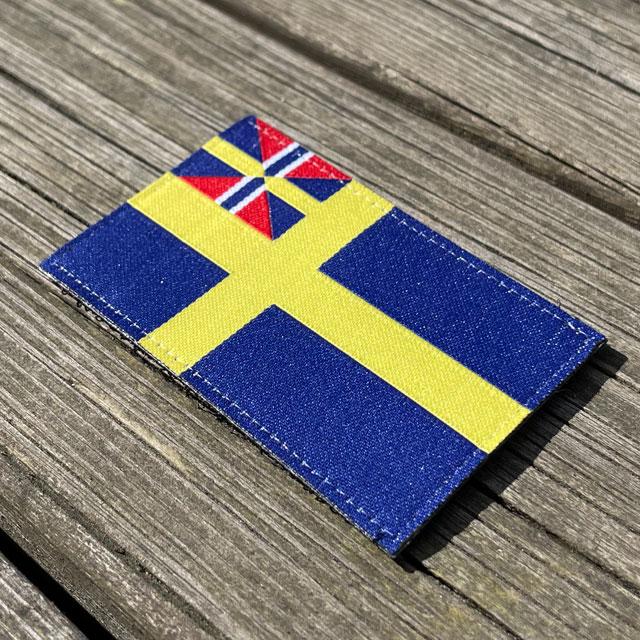 Sveriges handelsflagga 1844–1905 från TAC-UP GEAR sett från sidan liggandes på brädor