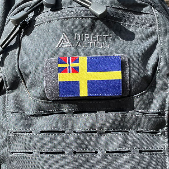 Ett Sveriges handelsflagga 1844–1905 från TAC-UP GEAR monterat på en grå ryggsäck sedd från sidan