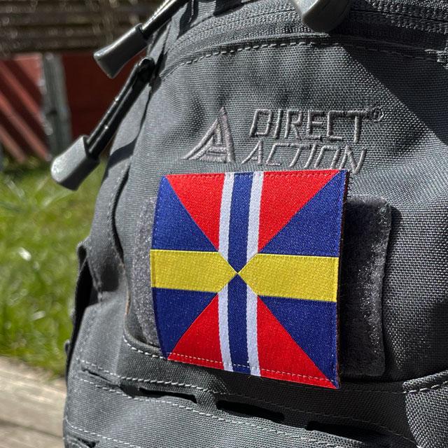 Ett Unionsmärket - Sillsalladen från TAC-UP GEAR sett från sidan på en grå ryggsäck
