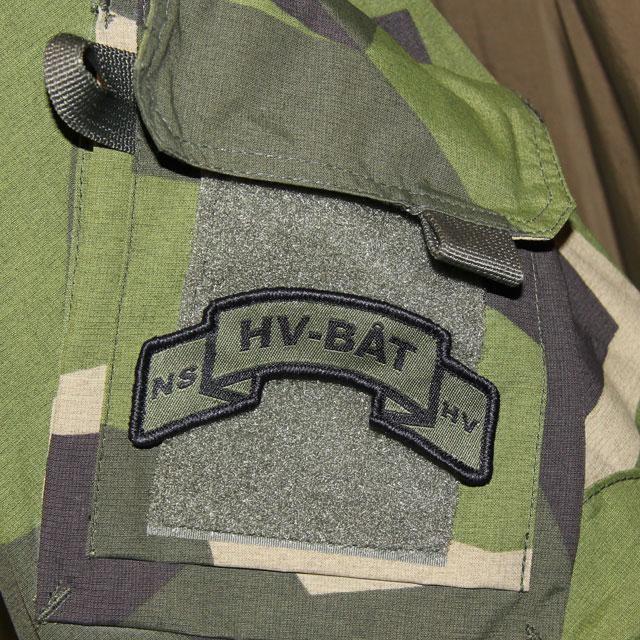 A mounted HV-BÅT Hook Scroll Patch on a M90 camouflage jacket.