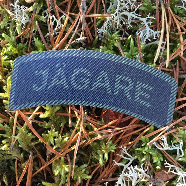 Utomhus foto på ett IR - JÄGARE Dual Grön/Svart märke med Svensk mossig skogsbakgrund.