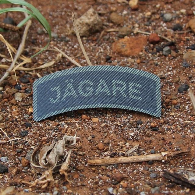 IR - JÄGARE Dual Grön/Svart produktbild med röd brun jord i bakgrunden.