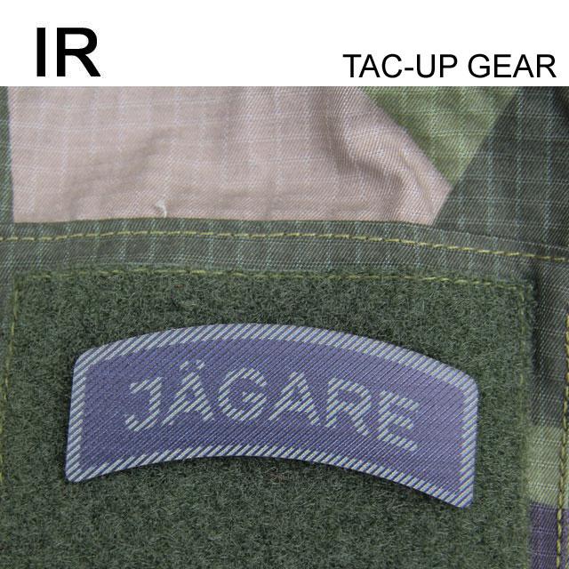 A IR - JÄGARE Dual Grön/Svart mounted on a M90 camouflage jacket.