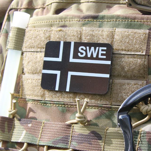 Ett IR - SWE Flagga IFF Svart/Grå märke på en stridsväst.