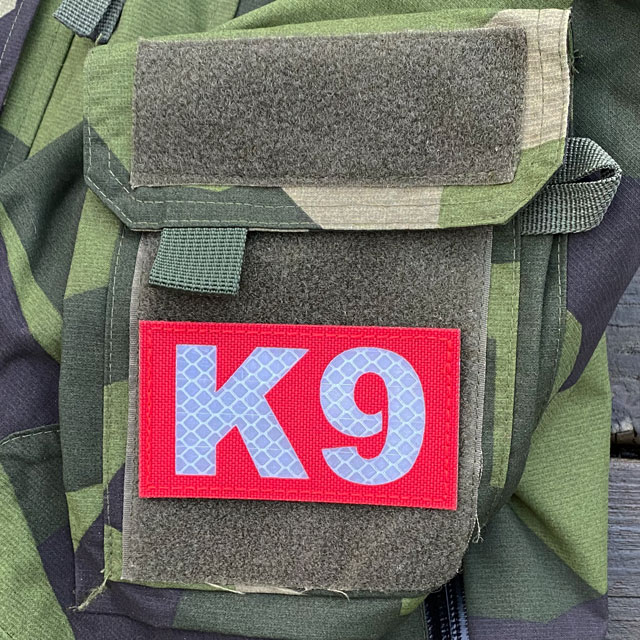 IR - K9 Red Hook Patch mounted on the sleeve of a M90 NCWR Jacket