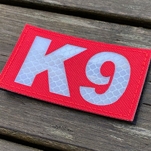A IR - K9 Red Hook Patch seen slightly from the side